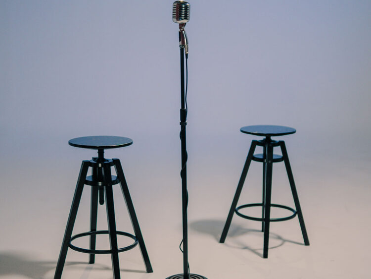 two stools around a microphone set up for interview
