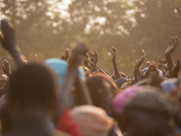 black congregation worshipping outdoors