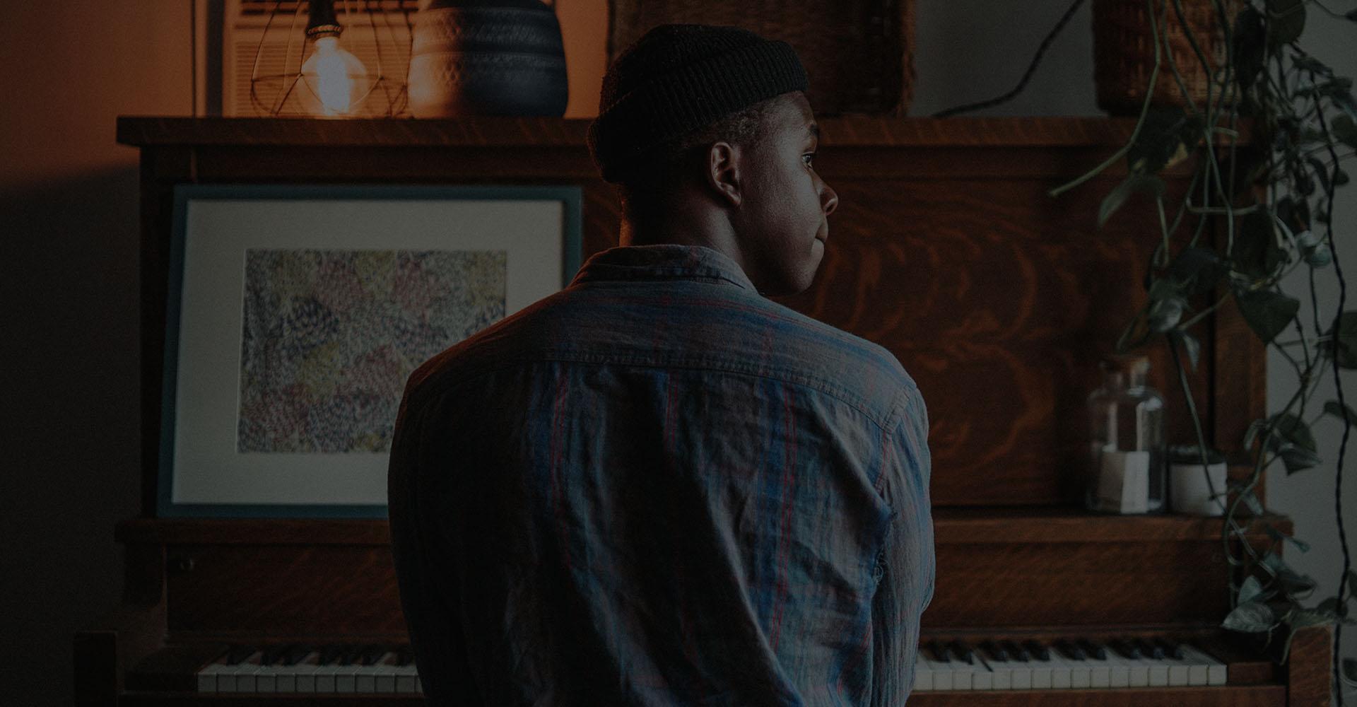 black man sitting at piano