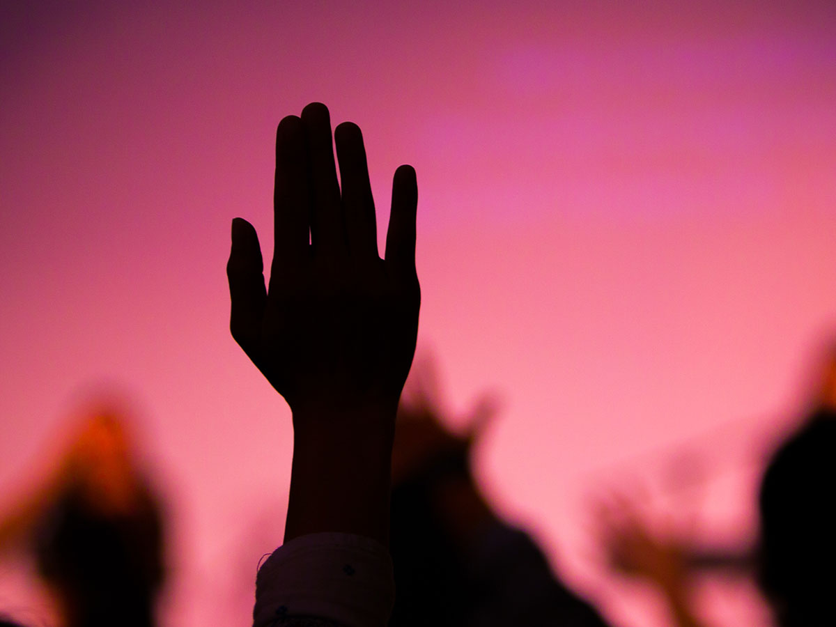 Silhouette of hands being raised up in a crowd